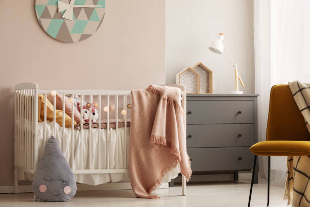 Pillows and toy in white wooden crib with pastel pink blanket in bright nursery Pillows and toy in white wooden crib with pastel pink blanket in bright nursery crib stock pictures, royalty-free photos & images