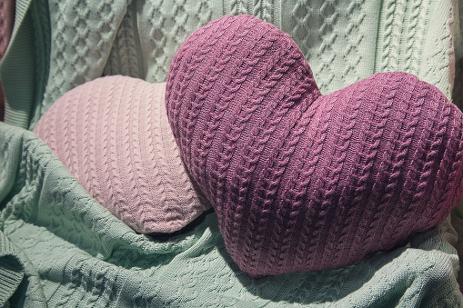 Pillows in the form of hearts and blankets on the bed. Romance