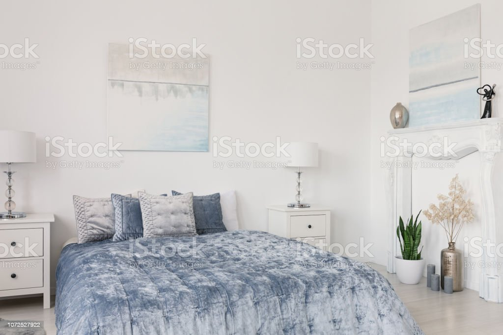 Picture of: Pillows On Blue Bed Between Lamps On Cabinets In White Bedroom Interior With Posters Real Photo Stock Photo Download Image Now Istock