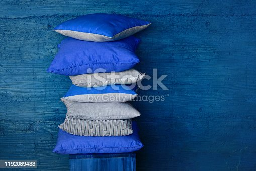 Stock of colorful pillows on wood chair against textured blue wall. Pile of soft blue cushions and blanket on stool near wall with space for text. Modern and cozy home concept.
