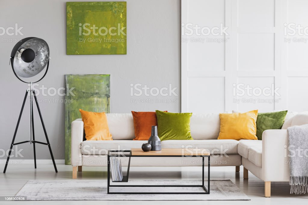 Pillows On Corner Sofa Next To Lamp In Living Room Interior With Green Posters And Table Real Photo Stock Photo - Download Image Now - IStock