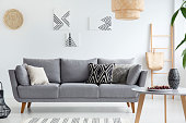 Pillows on grey sofa in white living room interior with posters, lamp and wooden table. Real photo