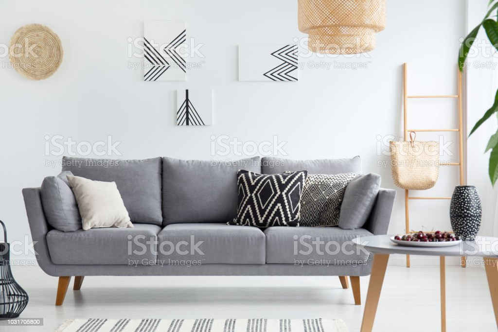 Pillows on grey sofa in white living room interior with posters, lamp and wooden table. Real photo stock photo