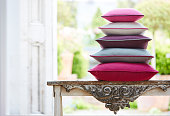 Shot of multi-colored pillows stack on old rustic table