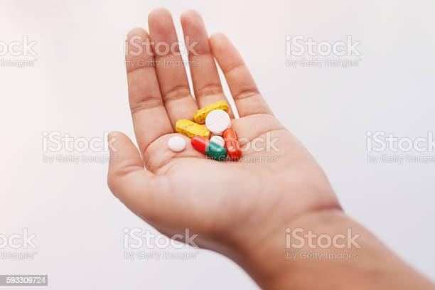 Pills - a source of treatment or trouble? Cropped shot of a hand holding an assortment of medication AIDS Stock Photo
