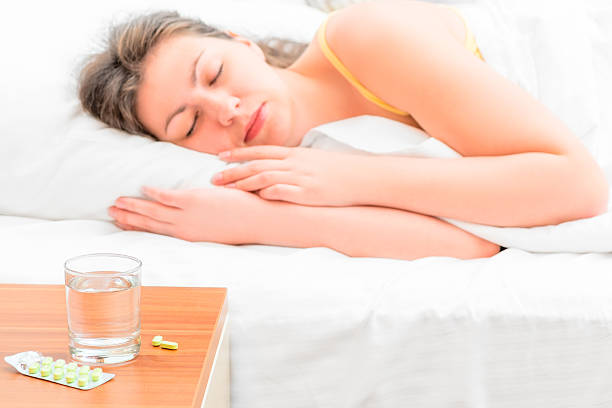 pills and a glass of water for the sick girl - sleeping pill stock photos and pictures