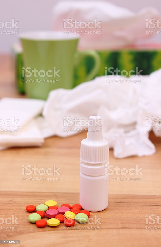 Pills and nose drops for colds, used handkerchiefs and hot tea in...