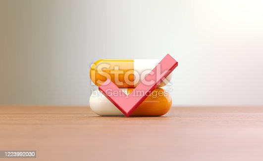 Yellow pills and red check mark sitting on brown wood surface in front of abstract defocused background. Horizontal composition with selective focus and copy space. Front view. Drug approval concept.
