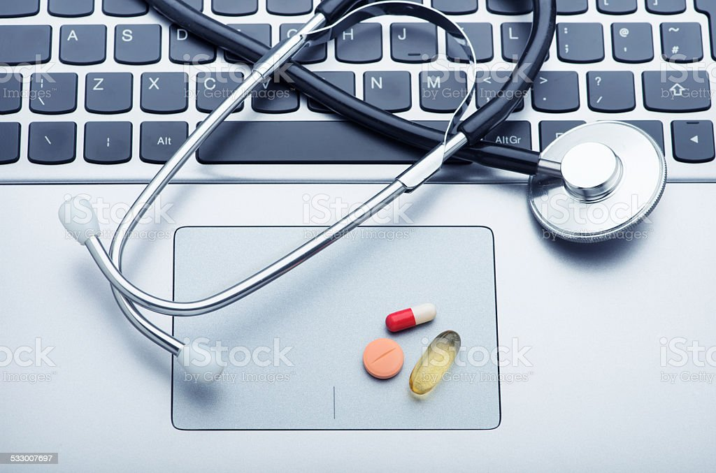 Pills and stethoscope on laptop stock photo