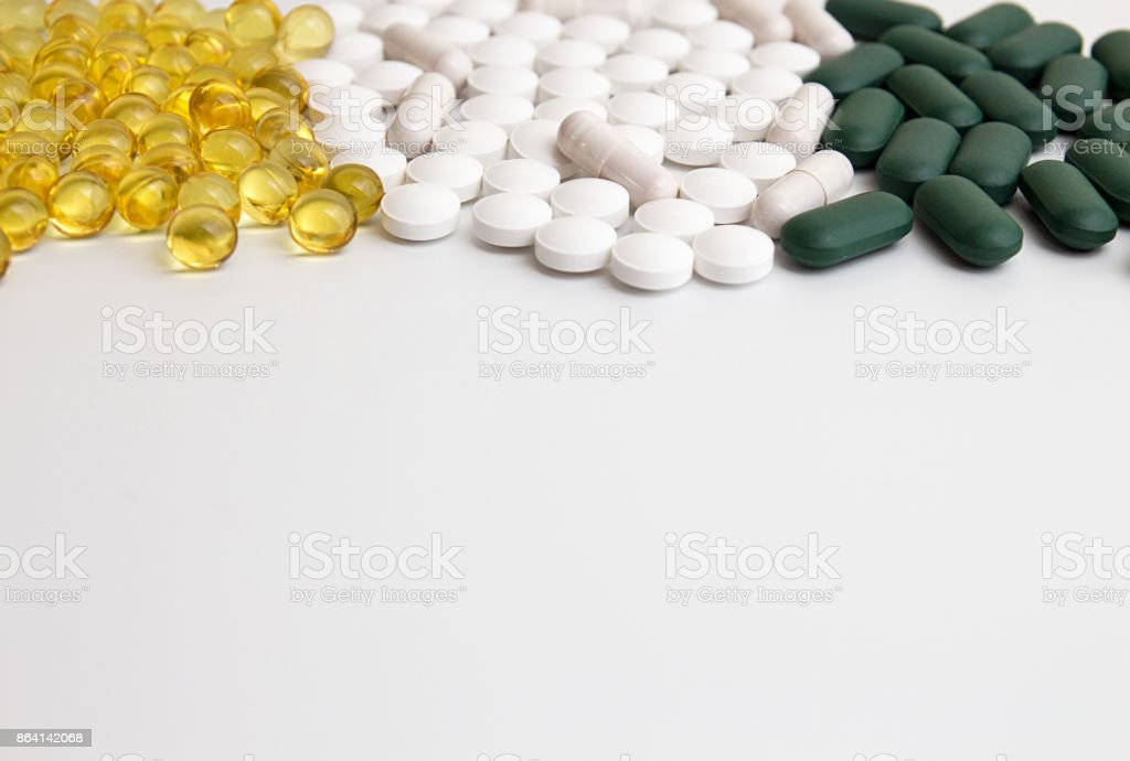 Pills background. Heap of assorted various medicine tablets and pills different colors on white background. Healthcare or medicament addiction concept. Copy space. royalty-free stock photo