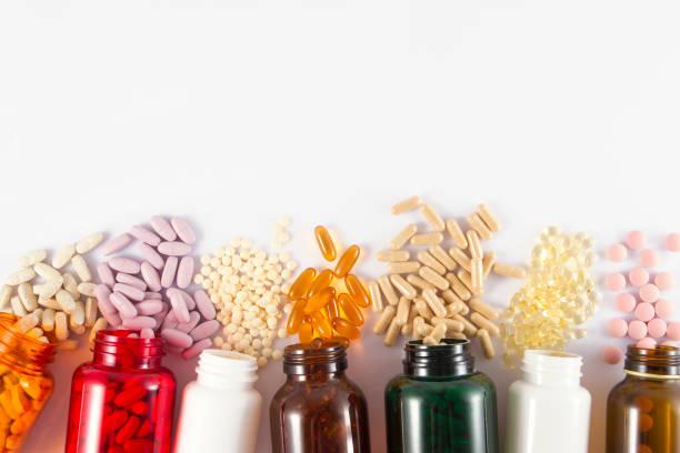 pillen im hintergrund - nahrungsergänzungsmittel stock-fotos und bilder
