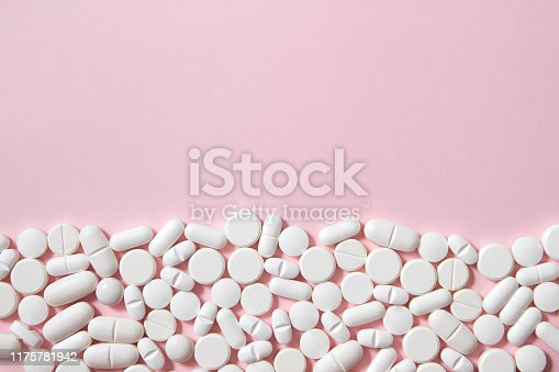 White pills over pastel pink background with copy space