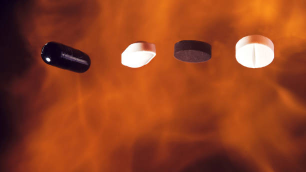 Pills burning in flame against black background. Drugs and medicine concept. stock photo