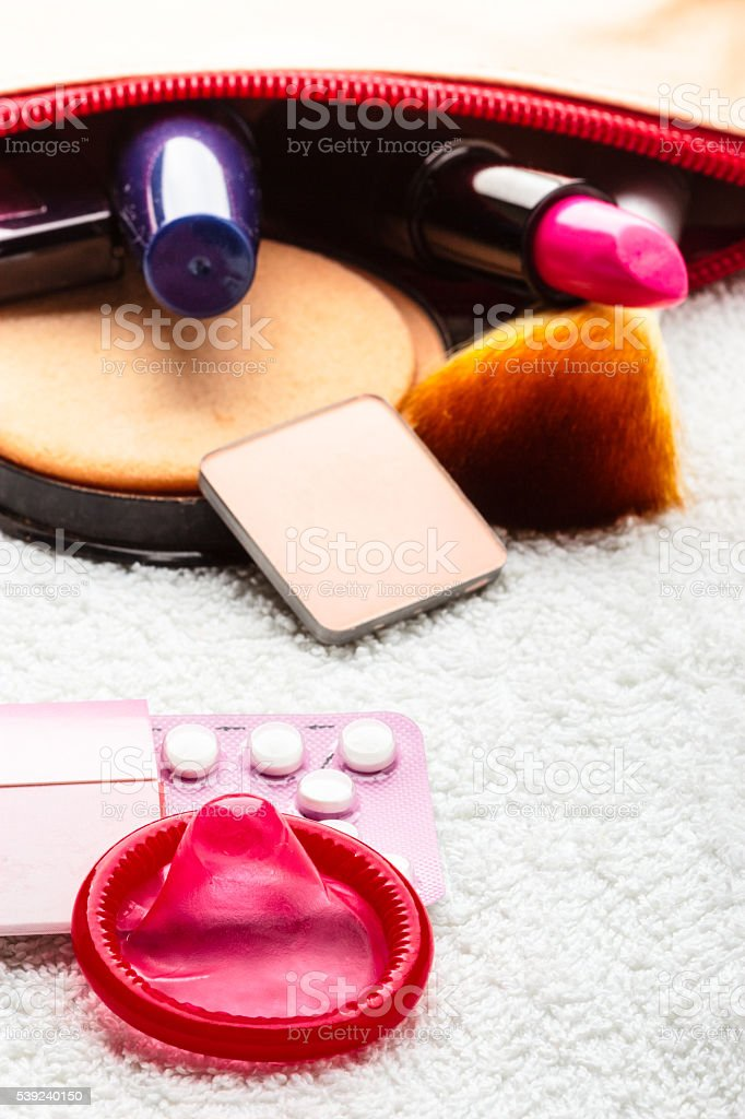 Pills, condom and cosmetics in handbag. royalty-free stock photo
