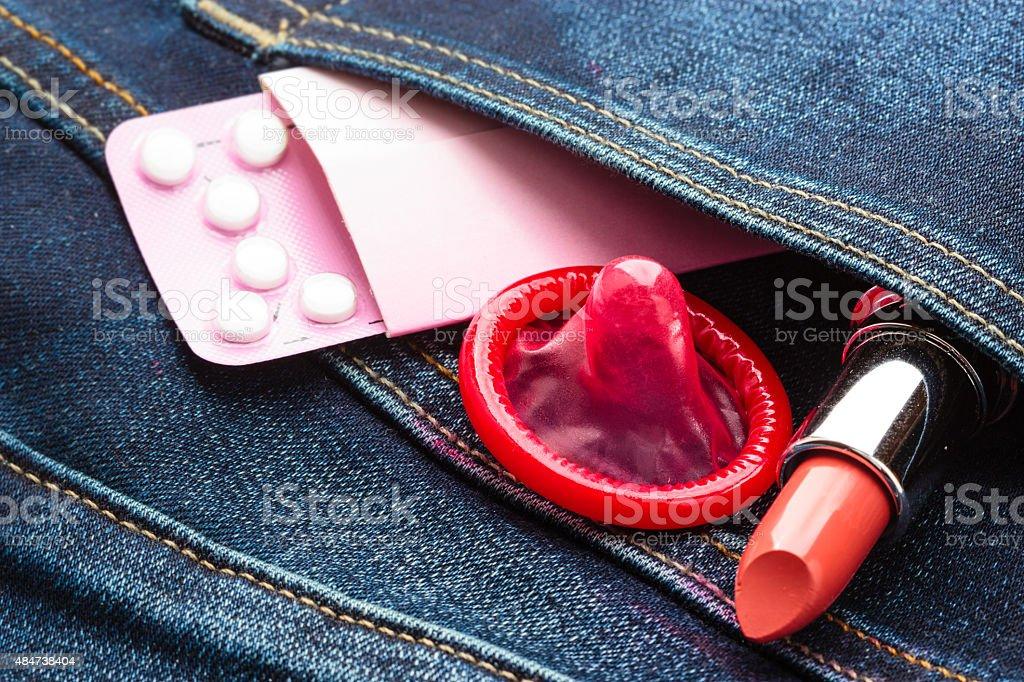 Pílulas Camisinha e batom em denim bolso. - foto de acervo
