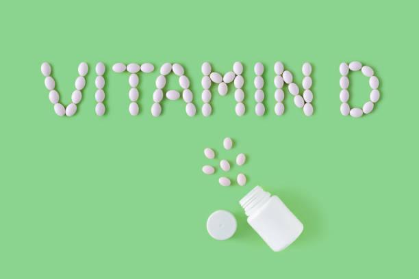 pills kelime şeklinde düştü yeşil arka planda şişe d vitamini. düz yatıyordu, üst görünüm. sağlık ve tıbbi kavram. - vitamin d stok fotoğraflar ve resimler