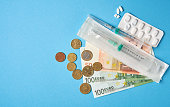 istock pills empty blisters for drugs individual syringe and money lie on a blue background 1205100283