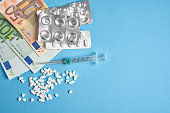 istock pills empty blisters for drugs individual syringe and money lie on a blue background 1205100321