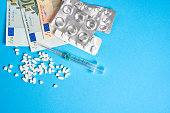 istock pills empty blisters for drugs individual syringe and money lie on a blue background 1264378234