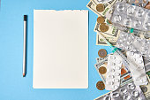istock pills empty blisters for drugs individual syringe and money lie on a blue background 1270707229