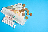 istock pills empty blisters for drugs individual syringe and money lie on a blue background 1279415577