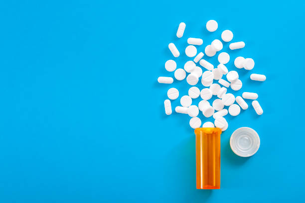 Pills falling from pill bottle on blue background with copyspace Medicine, opioid painkillers and prescription medicines concept with top view of orange prescription bottle of oxycodone and hydrocodone pills spilled on a blue background with copy space dependency stock pictures, royalty-free photos & images