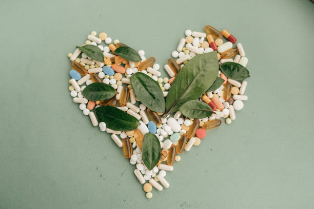 pills forming heart shape - vitamin stock photos and pictures
