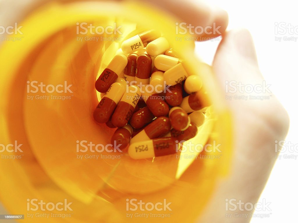 Pills in a bottle in a hand stock photo