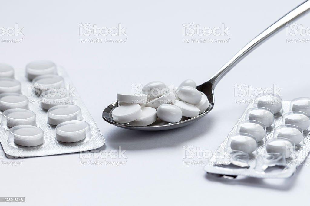 Pills In A Silver Spoon stock photo
