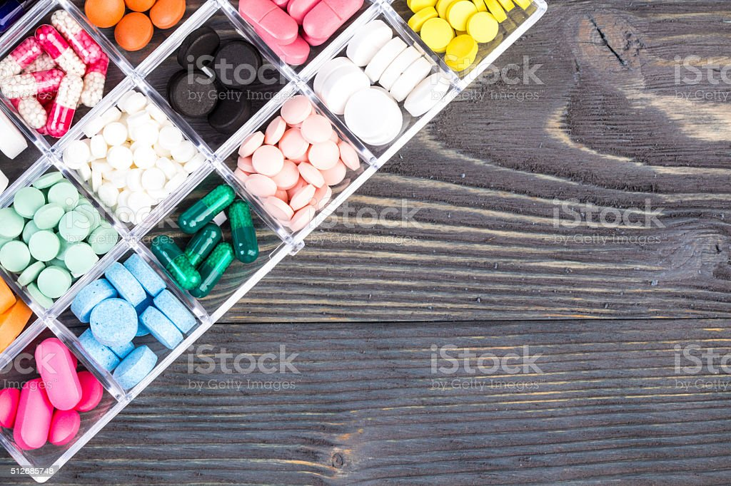 Pills in plastic container on wooden table stock photo