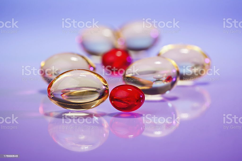 Pills (capsules) of cod-liver oil on violet, macro royalty-free stock photo