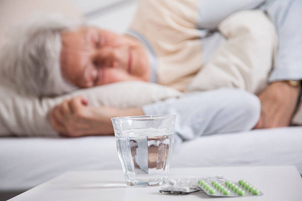 pills on a night table and senior woman sleeping - sleeping pill stock photos and pictures