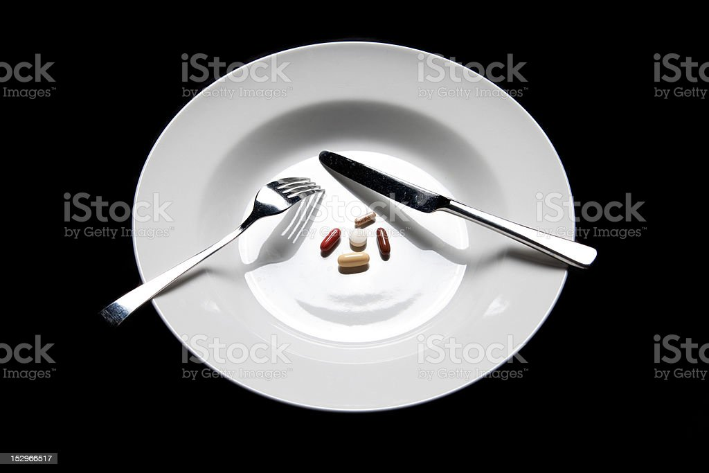 pills on a plate cutlery isolated royalty-free stock photo