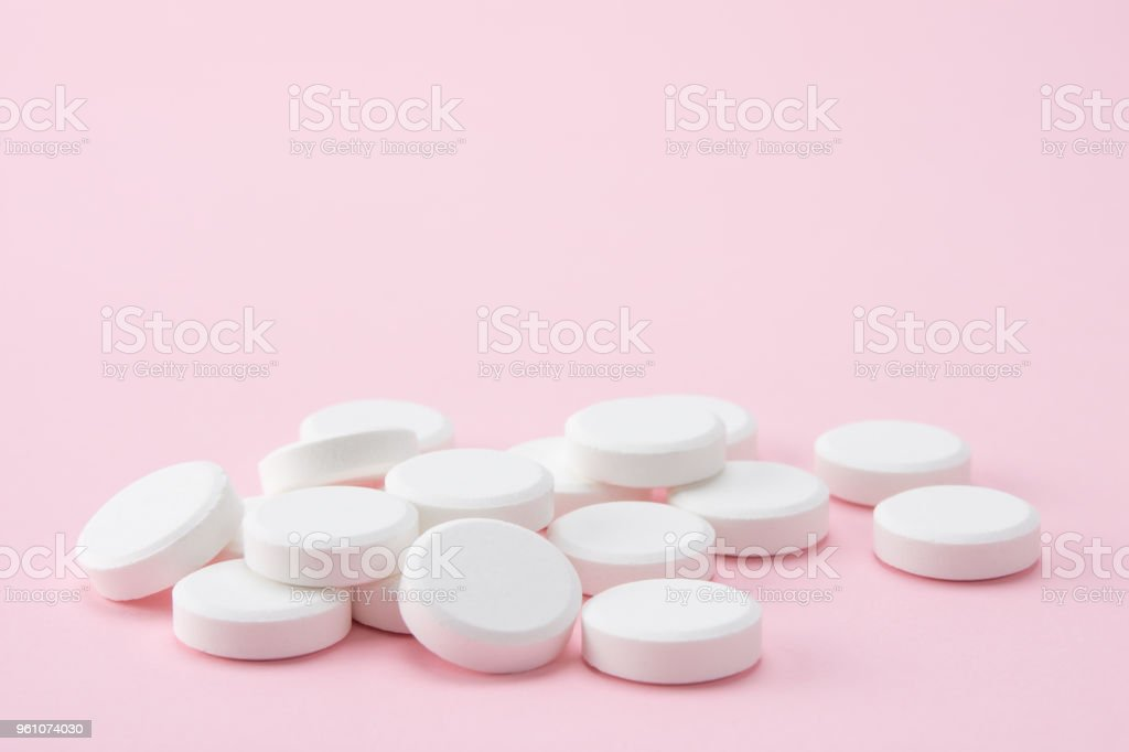 pills on pink background stock photo