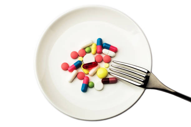 Pills on white plate with fork. Pill instead of food