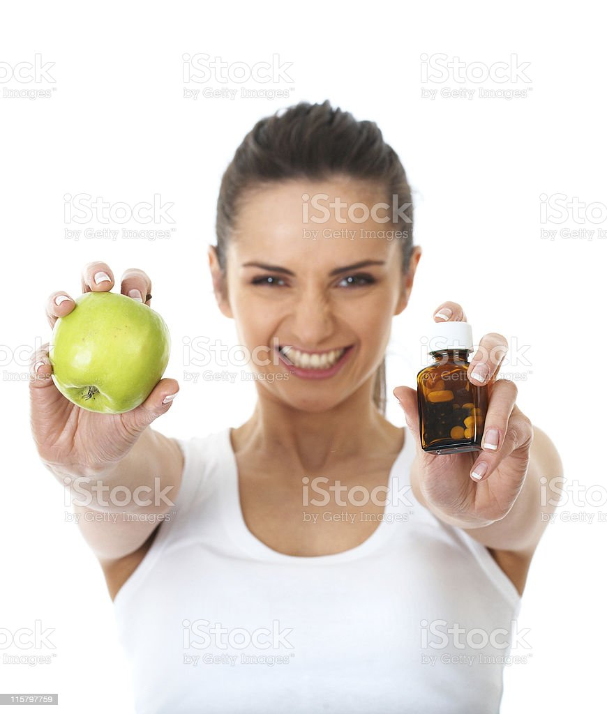 pills or apple, two sources of vitamins, isolated on white royalty-free stock photo