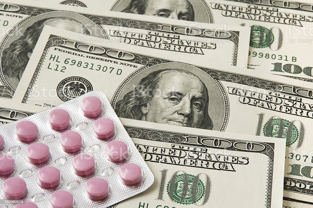 Pills package on money background royalty-free stock photo