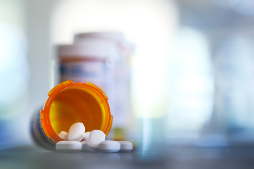 Pills pour out of a prescription medication bottle onto a kitchen counter.  Several other pill bottles stand out of focus in the background.
