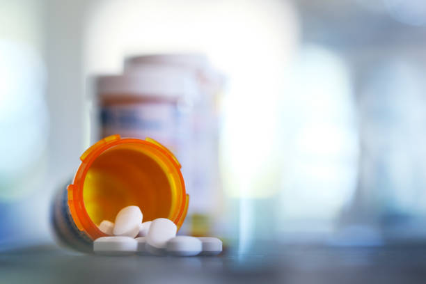 Pills Pour Out Of Prescription Medication Bottle Onto Kitchen Counter stock photo