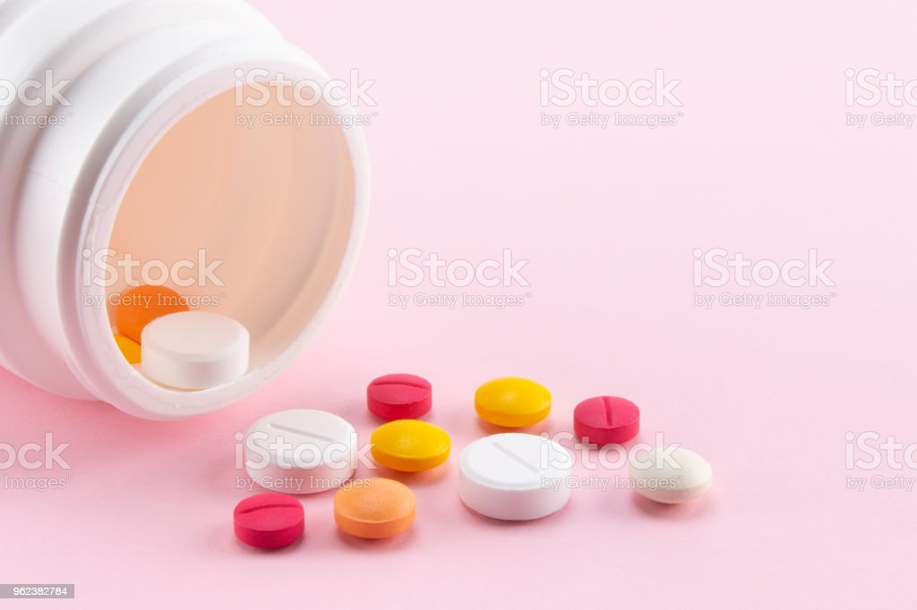 pills pouring out of the medcine bottle stock photo