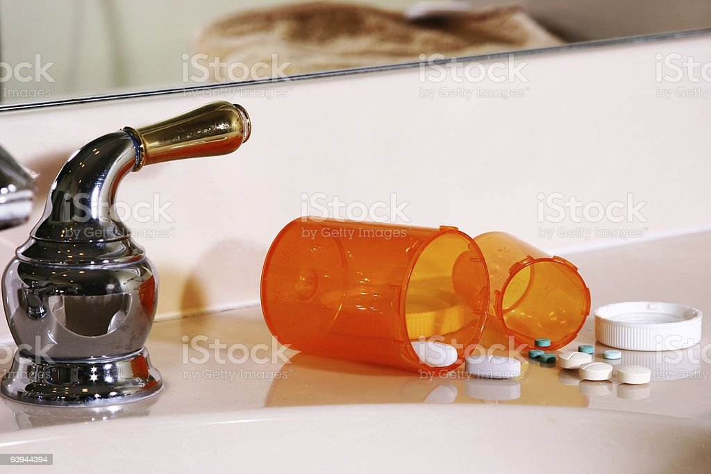 Pills spilled by bathroom sink royalty-free stock photo