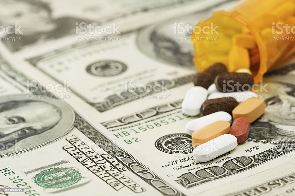 Pills spilled onto $100 bills royalty-free stock photo