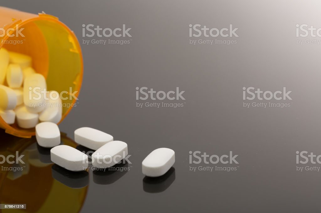 Pills spilled out on table stock photo