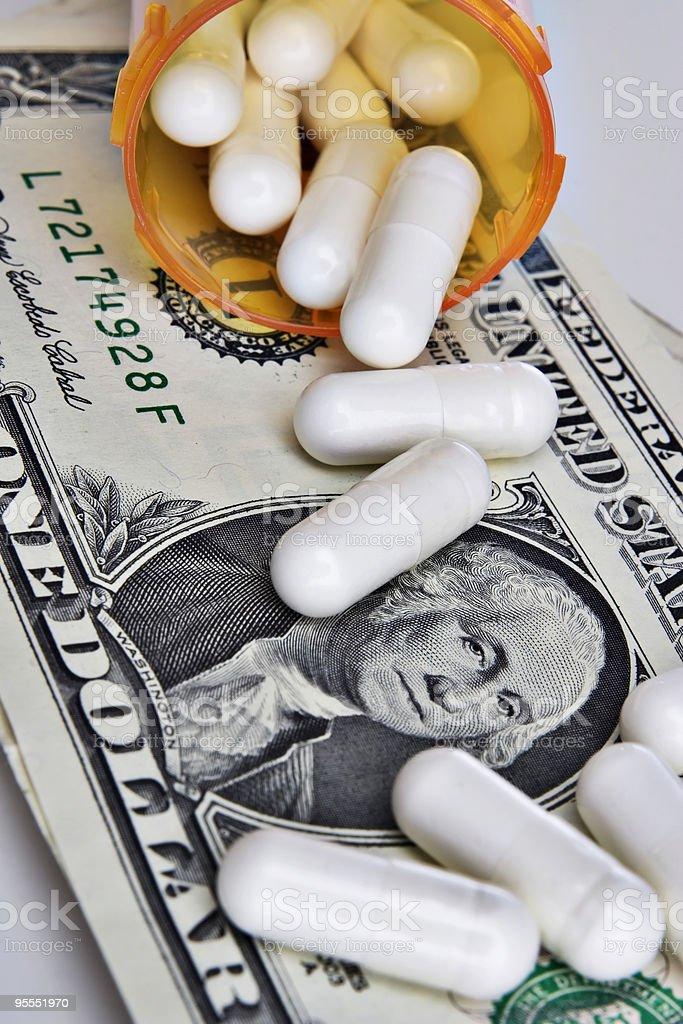 Pills spilling onto dollar royalty-free stock photo