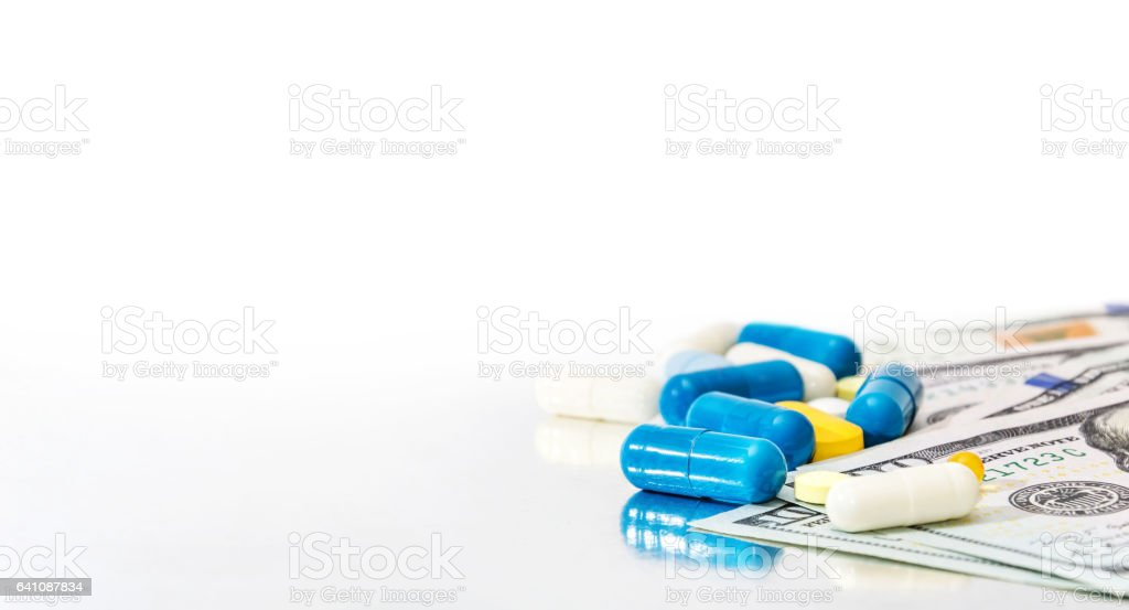 Pills with money on reflective background. stock photo