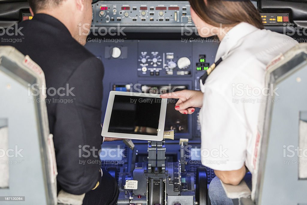 Pilot and Copilot Checking Flight Information on Digital Tablet stock photo