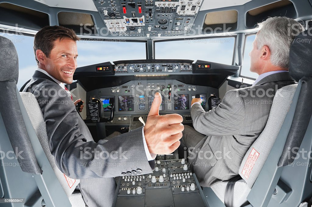 Pilot and co-pilot piloting airplane from airplane cockpit stock photo