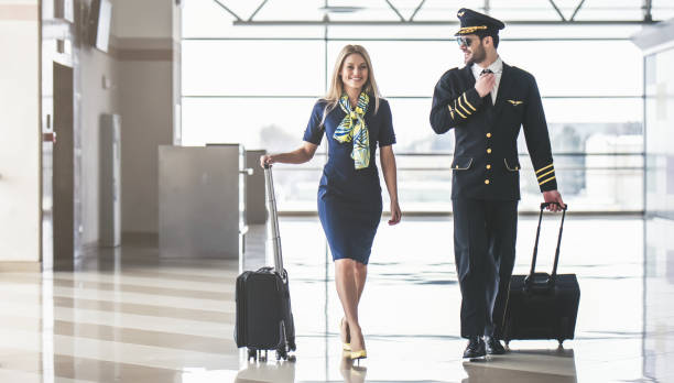 Pilot and flight attendant in airport Handsome male pilot and attractive female flight attendant are walking in airport terminal together. cabin crew stock pictures, royalty-free photos & images