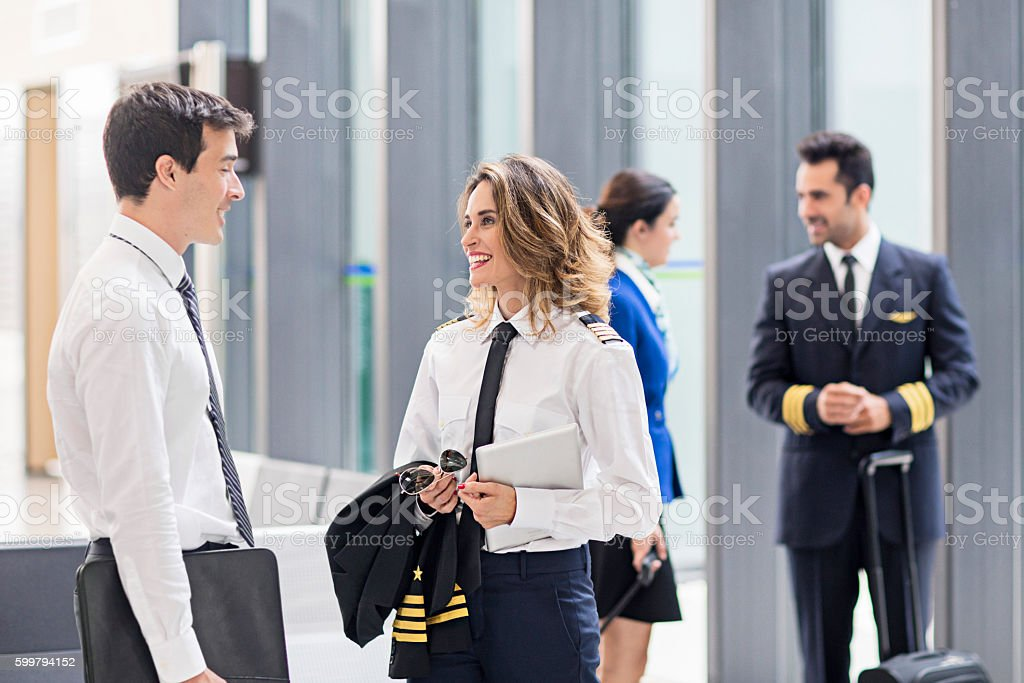 Pilot and flight attendants talking in the airport stock photo