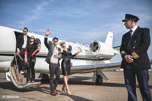 Nicely dressed celebrity people with sunglasses exiting the private jet airplane and pilot in front view is standing to escort them.